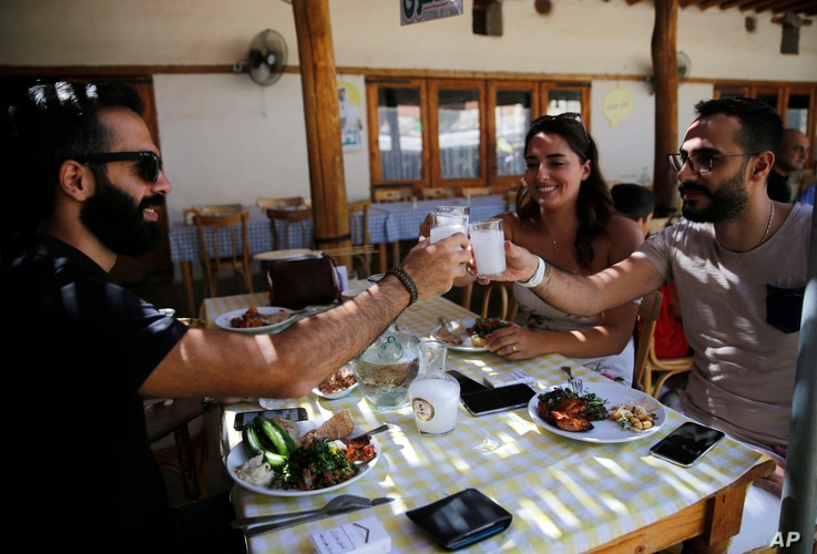 In this Sept. 8, 2018 photo, Lebanese raise their glasses of arak in a toast during a festival that celebrates Lebanon's national alcoholic drink, in the town of Taanayel, east Lebanon.