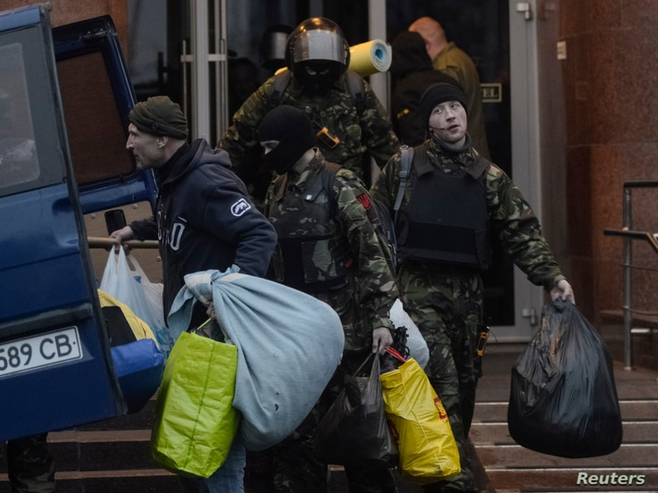 Members of the Ukrainian far-right radical group Right Sector leave their headquarters in Dnipro Hotel as police special forces stand guard, Kyiv, April 1, 2014.