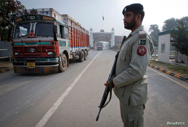 FILE - A paramilitary soldier stands guard as a truck crosses into Pakistan from India, at the Wagah border, Nov. 4, 2011.