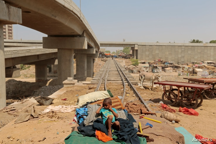 A child from a homeless family sits on a bed on the track of the disused Karachi Circular Railway line in Karachi, Pakistan, May 23, 2017.
