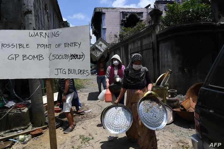 Residents carry belongings collected from their destroyed house during a visit to the main battle area in Marawi City, in southern island of Mindanao on April 1, 2018.