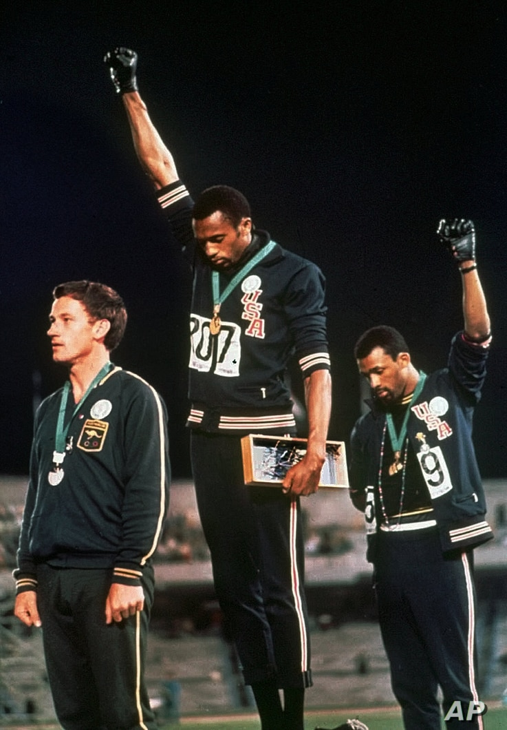 """Extending gloved hands skyward in racial protest, U.S. athletes Tommie Smith, center, and John Carlos stare downward during the playing of """"The Star-Spangled Banner""""  after Smith received the gold and Carlos the bronze medal in the 200 meter run at t..."""