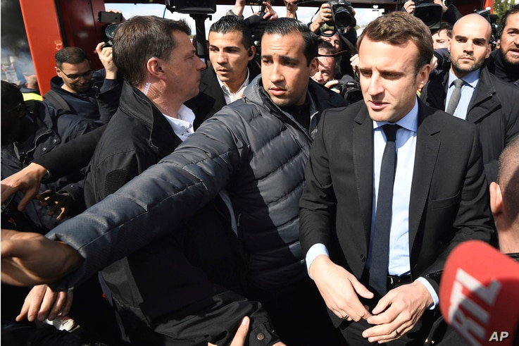 French centrist presidential election candidate Emmanuel Macron, flanked by his bodyguard, Alexandre Benalla, left, arrives outside the Whirlpool home appliance factory, in Amiens, northern France, April 26, 2017.