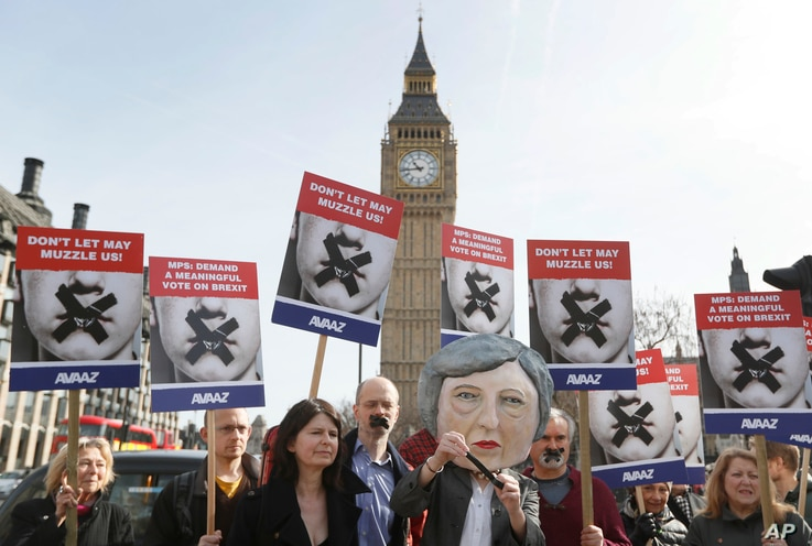 Demonstrators, one dressed in a Theresa May puppet head pose near parliament in London, March 13, 2017.
