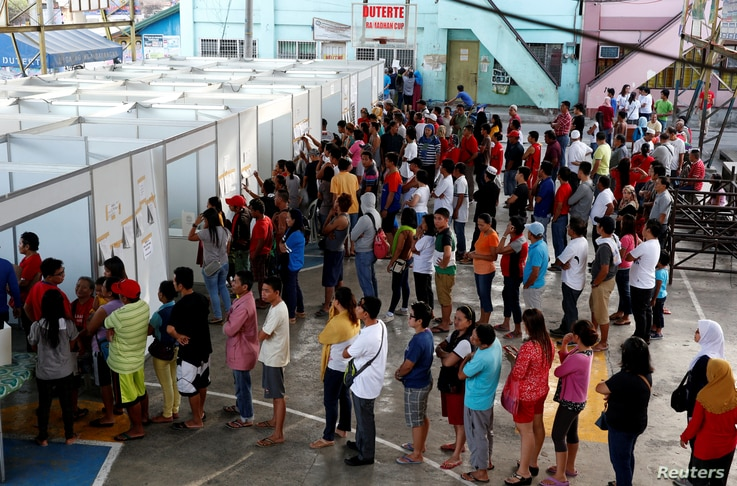 Residents queue in polling precincts to vote in national elections in Davao city, southern Philippines, May 9, 2016. Filipinos will choose a successor for President Benigno Aquino and candidates for 18,000 other elected offices.