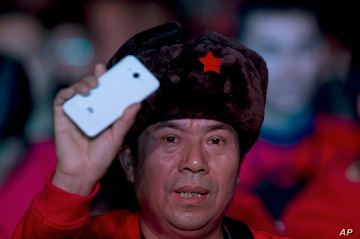 """FILE - A fan of Xiaomi (China's Apple) smartphone holds up one of the phones during a product unveiling event of the Chinese company in Beijing. Xiaomi is widely referred to as """"China's Apple,"""" and with handsets priced as low as $200, it may so..."""