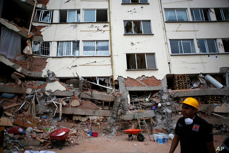 A rescue worker walks in front of an apartment building whose first four floors collapsed, in the Lindavista neighborhood of Mexico City, Sept. 20, 2017.