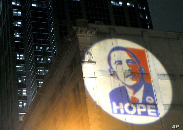 FILE - The poster of the campaign for President-elect Barack Obama is projected on the back wall of the Masonic Lodge Temple Building in Raleigh, N.C., Nov. 4, 2008.