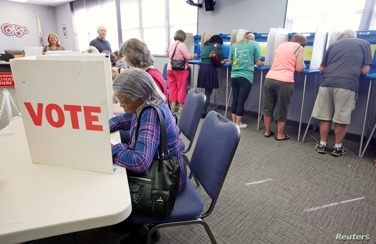 Voters fill in their ballots at a crowded polling station on North Carolina's first day of early voting for the general elections, in Carrboro, North Carolina, Oct. 20, 2016.