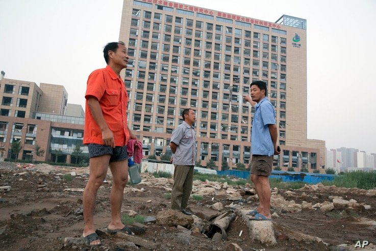 Workers walk near a building with windows shattered by the shockwave from a nearby explosion in northeastern China's Tianjin municipality, Aug. 13, 2015.