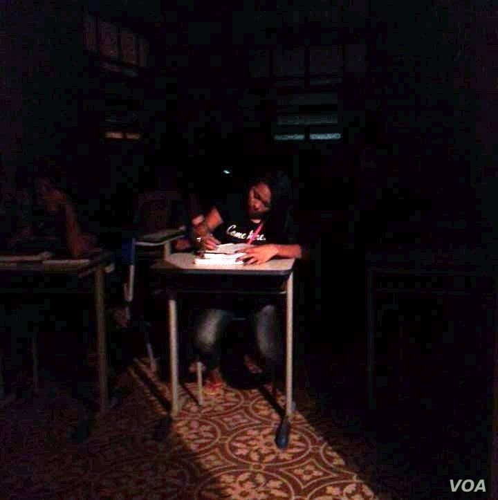 A Brazilian student is seen doing school work in a classroom without electricity. One of the Occupy Movement's demands is improvement of classroom conditions in every public school. (Photo – courtesy of Rafael Galvao)