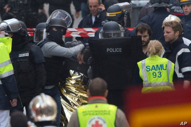 Hooded police officers detain a man in Saint-Denis, near Paris, after a raid on an apartment where the suspected mastermind of last week's terror attacks in the French capital was believed to have been holed up, Nov. 18, 2015.