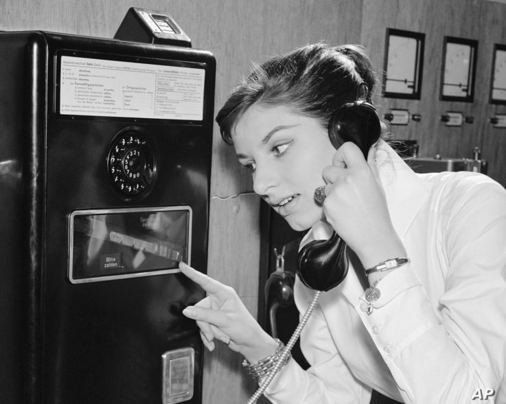 As coins slide down before her eyes, a German woman uses a new long distance dial telephone for public booths, July 17,1957.(AP Photo)