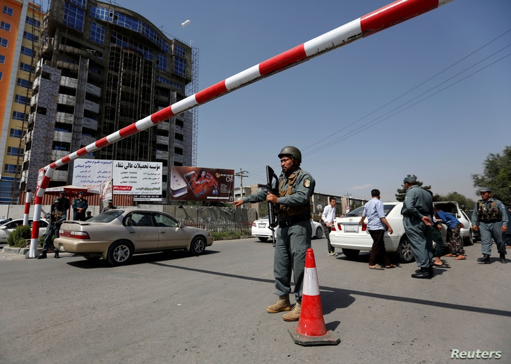 An Afghan police officer inspects vehicles at a checkpoint in Kabul, Afghanistan, Aug. 6, 2017.