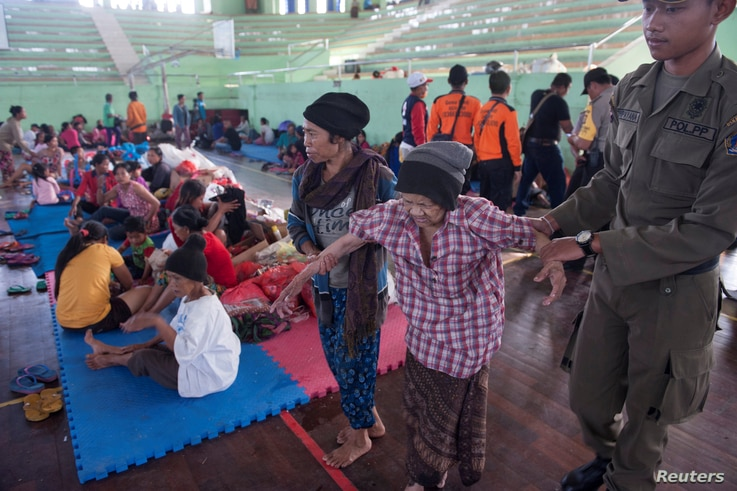 An evacuated villager from locations near the summit of Mount Agung, an active volcano which is showing increased seismic activity, is helped at a temporary shelter in Klungkung, on the resort island of Bali, Indonesia, Sept. 22, 2017 in this photo t...