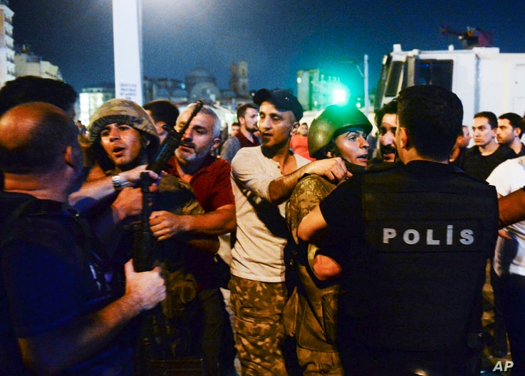 Turkish soldiers, arrested by civilians after an attempted coup, are handed to police officers in Istanbul on July 16, 2016.