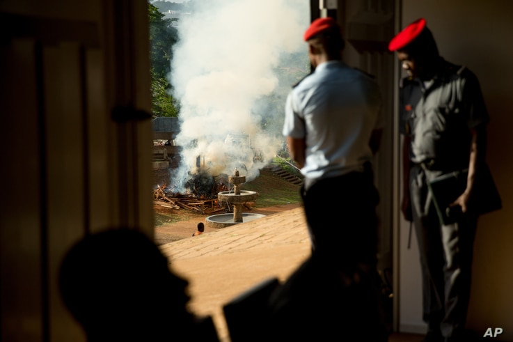 FILE - Officials watch from a distance as a pile of some 2,000 illegally trafficked elephant tusks and hundreds of finished ivory products are destroyed in the first ever Cameroonian burn of poached wildlife goods, April 19, 2016.