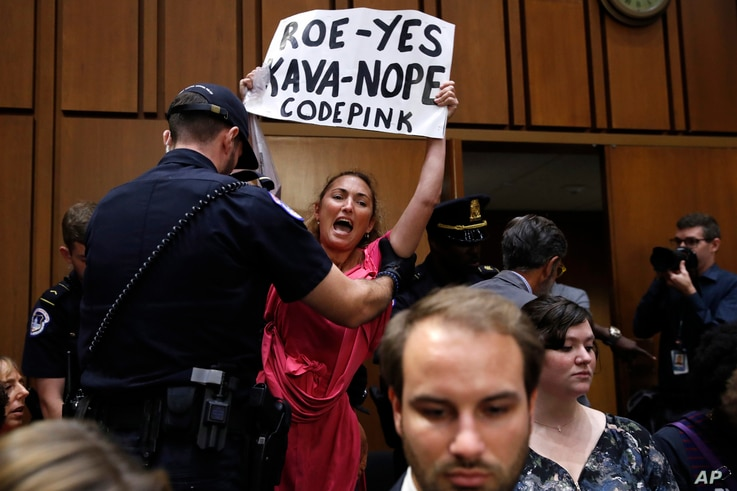 A woman stands and voices her opposition to Supreme Court nominee Brett Kavanaugh, during a Senate Judiciary Committee confirmation hearing on his nomination for Supreme Court, on Capitol Hill, Sept. 4, 2018, in Washington.