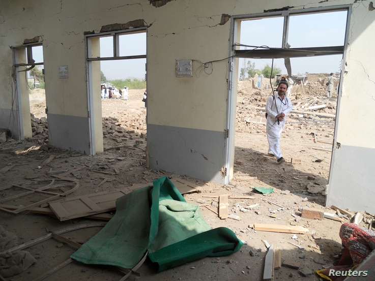 A member of the media walks past a damaged mosque at the site of a bomb attack in the Spin Tal region of Hangu district, Pakistan, Oct. 3, 2013.
