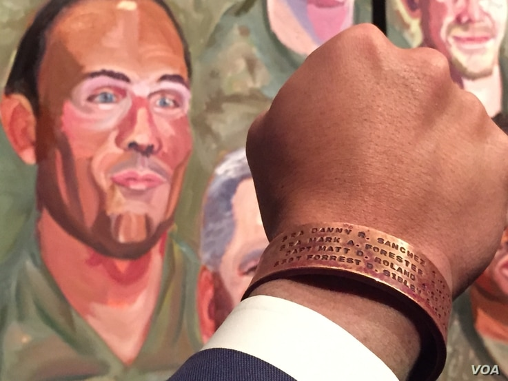 "Johnnie Yellock holds his hand next to his portrait painted by former president George W. Bush. The bracelet on Yellock's hand bears the names of four of his personal heroes. ""Those that don't come home ... those are the heroes of our time,"" he..."