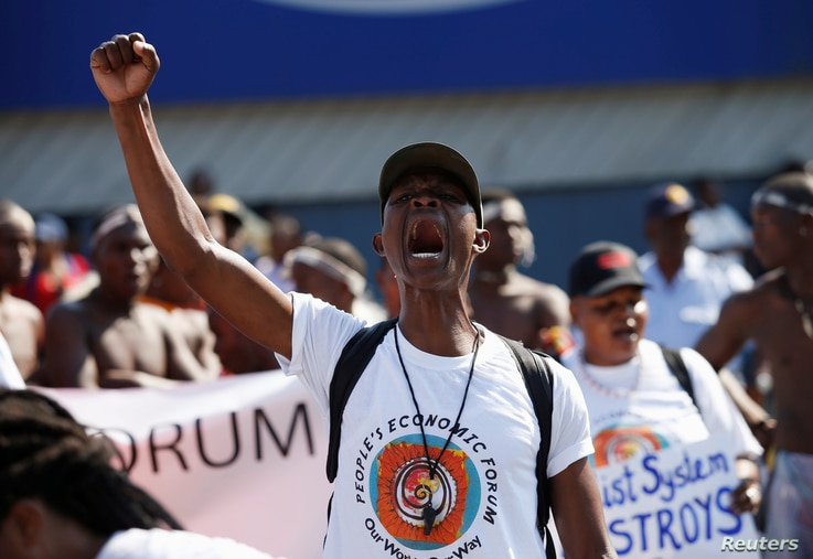 Protesters march past the venue for the World Economic Forum on Africa 2017 meeting in Durban, South Africa, May 3, 2017.