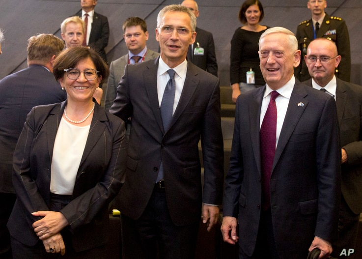 Italian Defense Minister Elisabetta Trenta, left, poses with NATO Secretary General Jens Stoltenberg, center, and U.S. Secretary for Defense Jim Mattis during a meeting of NATO defense ministers in Brussels, June 7, 2018.