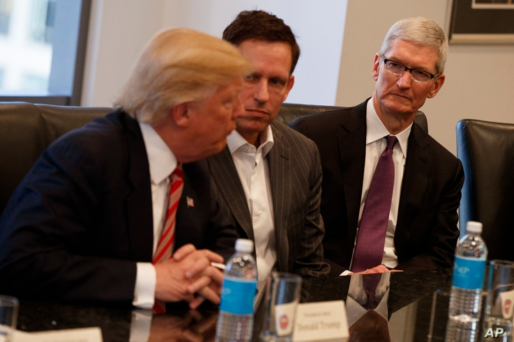 Apple CEO Tim Cook, right, and PayPal founder Peter Thiel, center, listen as President-elect Donald Trump speaks during a meeting with technology industry leaders at Trump Tower in New York, Dec. 14, 2016.