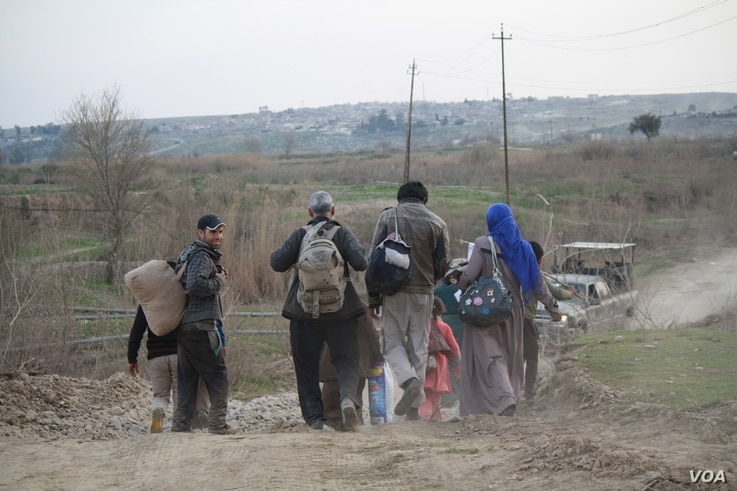 On the outskirts of the battlefields families continue to walk to Iraqi-controlled areas, carrying only a few belongings and white flags to signal they are not militants, in Mosul, Iraq, Feb. 28, 2017. (H. Murdock/VOA)