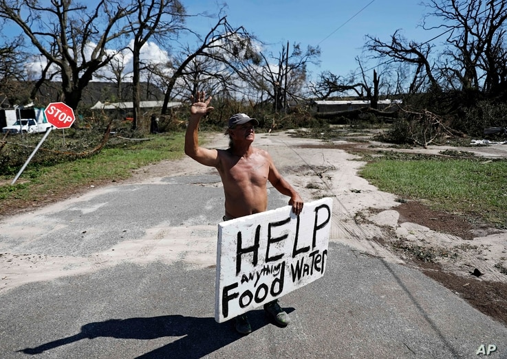 Michael Williams, 70, waves to passing motorists while looking for food and water as downed trees prevent him from driving out of his damaged home with his family in the aftermath of Hurricane Michael in Springfield, Fla., Oct. 11, 2018.