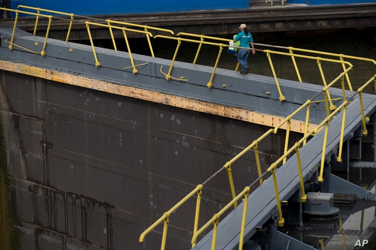 A worker walks across the Miraflores Locks during a press tour of the Panama Canal in Panama City, June 25, 2016. The $5.25 billion expansion of the canal will allow larger ships to pass, increasing efficiency.