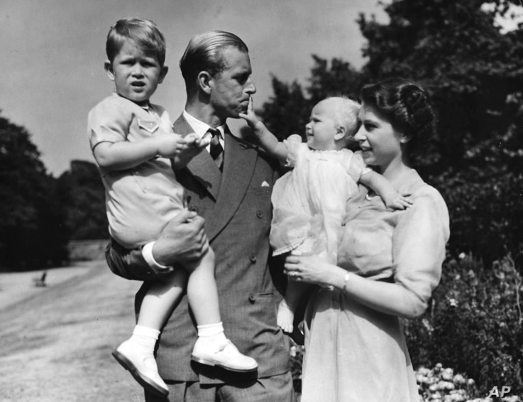 FILE - In this August 1951 file photo, then-Princess Elizabeth stands with her husband Prince Philip, the Duke of Edinburgh, and their children Prince Charles and Princess Anne at the couple's London residence at Clarence House.