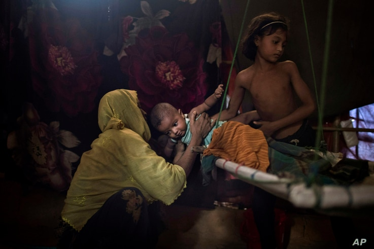 "M's daughter  hands over her baby brother to their mother in their shelter in Kutupalong refugee camp, June 26, 2018. ""M"" was raped by six soldiers from Myanmar's security forces after they strangled her 2-year-old son to death."