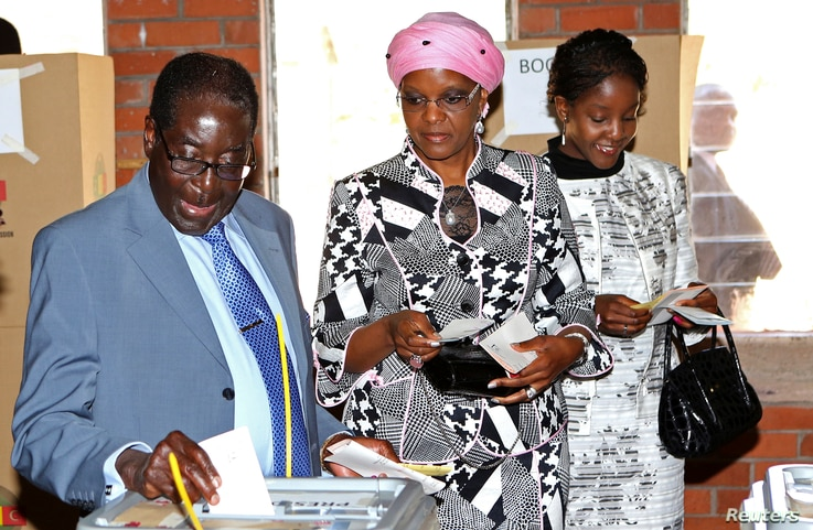 FILE - Zimbabwe's President Robert Mugabe casts his vote as his wife Grace and daughter Bona (L-R) look on in Highfields outside Harare, July 31, 2013.