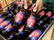 """A worker poses with bottles of """"Kiss Me Kate"""" ale at a Morrisons supermarket in Leicester."""