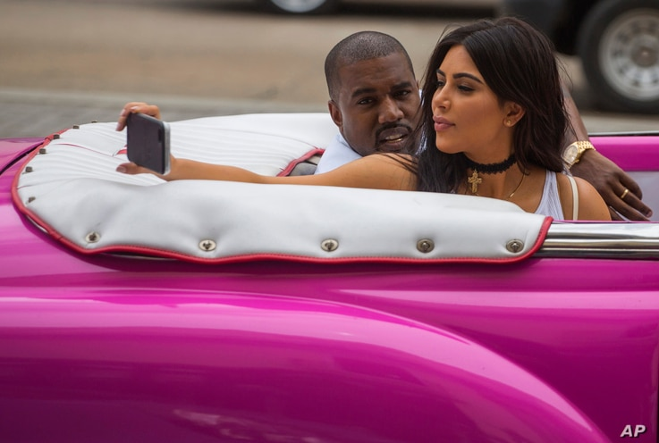 American reality-show star Kim Kardashian takes a selfie as she rides on a classic car next to her husband, rap singer Kanye West in Havana, Cuba on May 4, 2016.