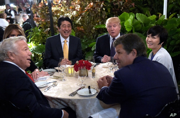 President Donald Trump, third from right, and first lady Melania Trump, hidden at left, sit down to dinner with Japanese Prime Minister Shinzo Abe, third from left, and his wife Akie Abe, right, at Mar-a-Lago in Palm Beach, Florida, Feb. 10, 2017.