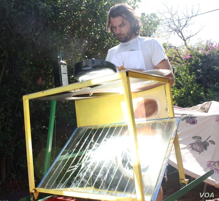 SunFire solar power technologist Zander van Manen cooks on the Sol-4, with sunlight reflected onto a pan. (Darren Taylor for VOA)