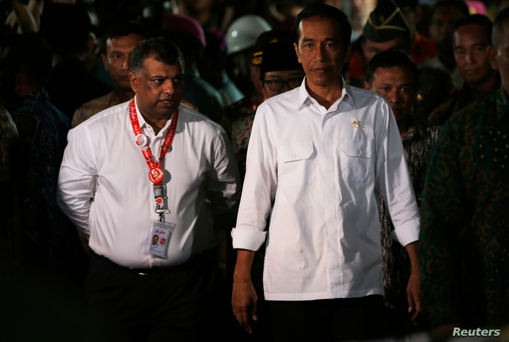 Indonesia's President Joko Widodo, right, walks beside AirAsia's CEO Tony Fernandes after meeting with family members of passengers onboard AirAsia flight QZ8501 in Juanda International Airport, Surabaya, Dec. 30, 2014.
