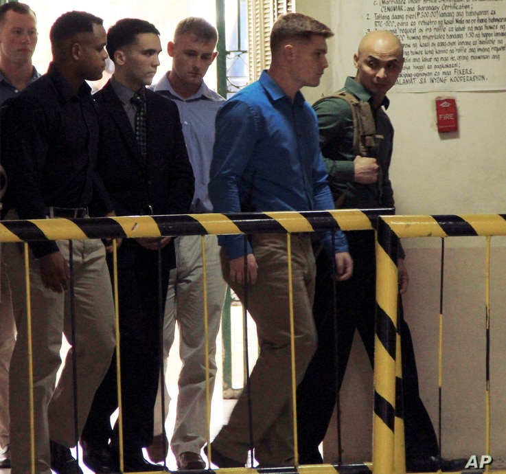 U.S. Marine Pfc. Joseph Scott Pemberton, third left, the suspect in the killing of Filipino transgender Jennifer Laude, is escorted into the courtroom for his scheduled trial, March 23, 2015, at Olongapo city, Zambales province, northwest of Manila, ...