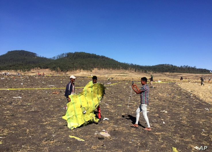 A civilian takes a photograph of the wreckage at the scene of the Ethiopian Airlines Flight ET 302 plane crash, March 10, 2019.