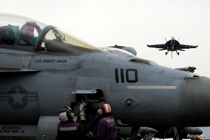 U.S. Navy sailors perform checks on a F-18 fighter jet as another F-18 prepares to land on the USS Harry S. Truman aircraft carrier in the eastern Mediterranean Sea, May 4, 2018.