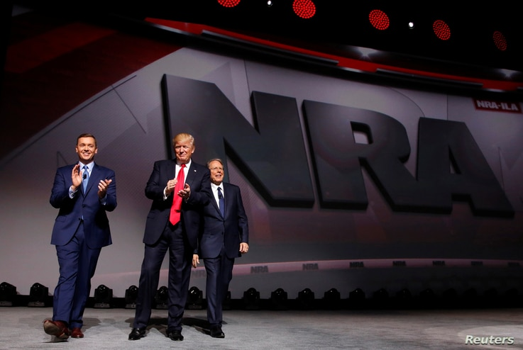 FILE - NRA Executive Director Chris Cox, left, and Executive Vice President and CEO Wayne LaPierre, right, welcome U.S. President Donald Trump onstage to deliver remarks at the National Rifle Association (NRA) Leadership Forum at the Georgia World Co...