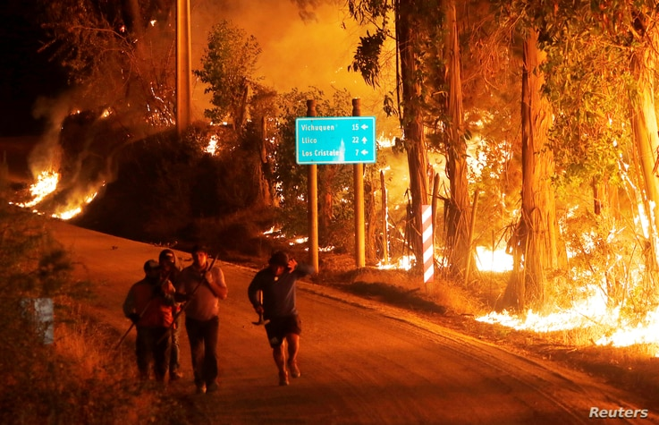 Fire is seen along a road in the town of Hualane during a big forest fire, on the outskirts of the Curico city, south of Chile, January 21, 2017