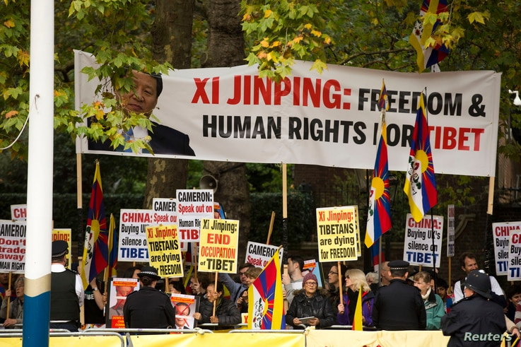 Human rights demonstrators hold up a protest banner bearing an image of Chinese President Xi Jinping before he passed by on a horse-drawn carriage with Britain's Queen Elizabeth II on the Mall en route to Buckingham Palace in London, Oct. 20, 2015.