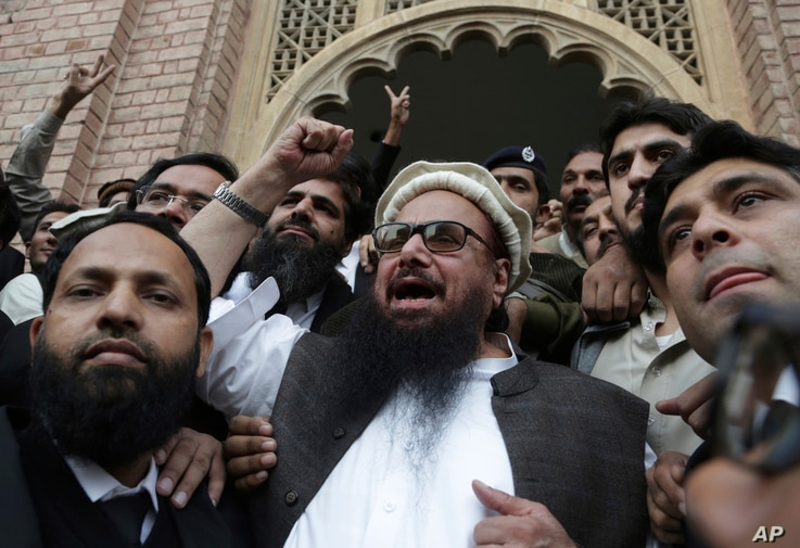 Hafiz Saeed, head of the Pakistani religious party, Jamaat-ud-Dawa, gestures outside a court in Lahore, Pakistan, Nov. 22, 2017. The court rejected the government's plea to extend for three months the house arrest of Saeed, the former leader of a ban...