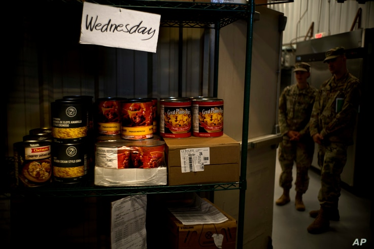 This Tuesday, June 5, 2018 photo reviewed by U.S. military officials shows a shelf lined with canned goods that includes food slated for the detainees' Wednesday menu, at the Guantanamo Bay U.S. Naval Base, in Cuba.