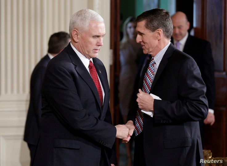 Vice President Mike Pence greets National Security Advisor Michael Flynn before Japanese Prime Minister Shinzo Abe and U.S. President Donald Trump arrive for their joint news conference at the White House in Washington, Feb. 10, 2017.