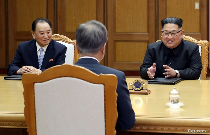 North Korean leader Kim Jong Un talks with South Korean President Moon Jae-in as Kim Yong Chol, North Korea's Vice-chairman of the central committee of the Workers' Party of Korea (WPK), listens during their summit at the truce village of Panmunjom, ...