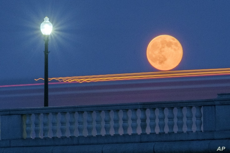 Traffic streaks by the supermoon as it rises behind the Memorial Bridge in Washington, Saturday, July 12, 2014. The full moon Saturday may seem huge, but it's just an illusion caused by its position in the sky. (AP Photo/J. David Ake)