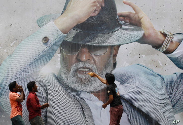 """Fans of Indian superstar Rajinikanth offer prayers in front of his poster outside a cinema hall to celebrate the screening of """"Kabali"""" in Chennai, India, Friday, July 22, 2016."""